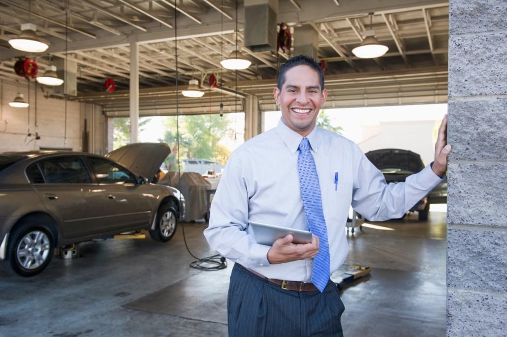 Hispanic businessman standing in auto repair shop