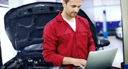Automotive mechanic using a laptop to run diagnostics on a vehicle he is repairing